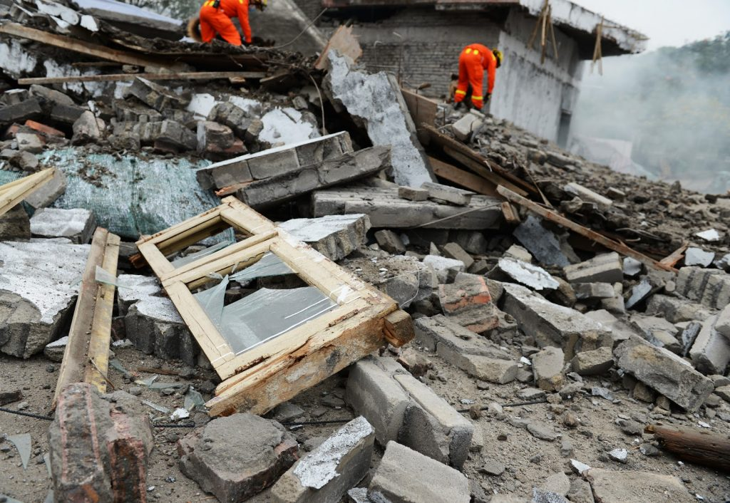 Men in orange jumpsuits searching through the wreckage ofa  destroyed home